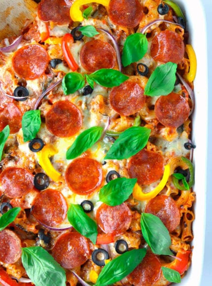 Top view of pizza pasta casserole garnished with basil leaves in a baking dish.