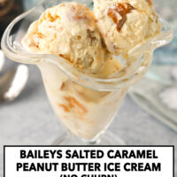 """Close-up front view of dessert glass with ice cream scoops. Text overlay """"Baileys Salted Caramel Peanut Butter Ice Cream (No Churn)"""" and """"thatspicychick.com""""."""