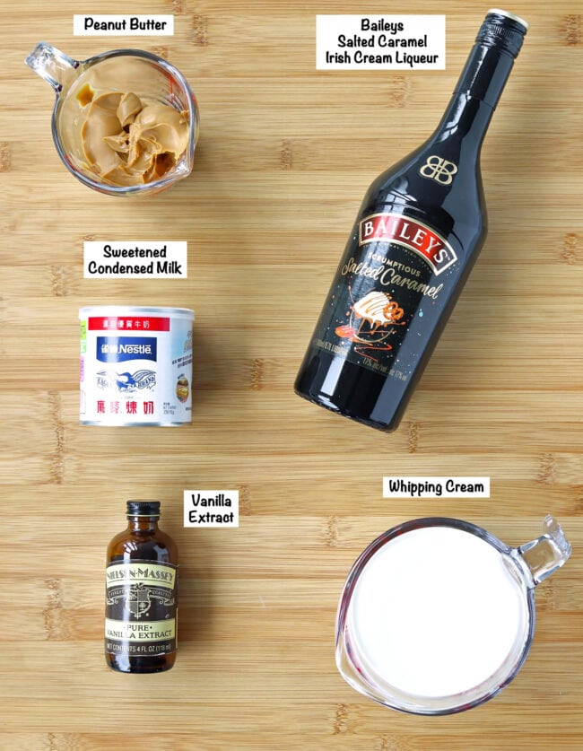 Labeled ingredients for Baileys Salted Caramel Peanut Butter Ice Cream on a wooden board.