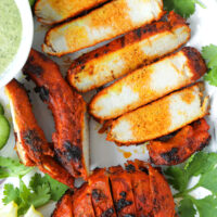 """Close-up of grilled sliced pork on a plate with garnishes. Text overlay """"Grilled Spicy Indian Pork Cutlets"""" and """"thatspicychick.com""""."""