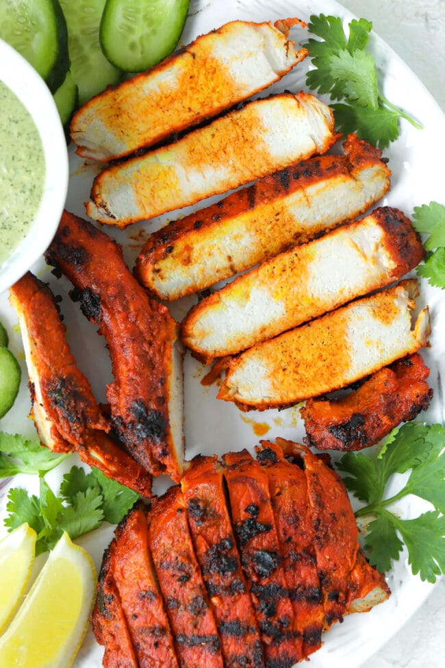 Top view close-up of grilled Indian pork slices on a plate.