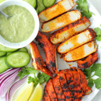 """Top view of plate with Indian-style grilled pork and garnishes. Text overlay """"Indian Grilled Juicy Pork Cutlets"""" and """"thatspicychick.com""""."""