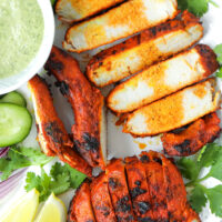 """Close-up top view of grilled sliced Indian pork on a plate with garnishes. Text overlay """"Grilled Indian Pork Cutlets"""" and """"thatspicychick.com""""."""