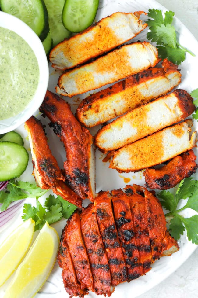 Close-up top view of plate with grilled pork, cilantro mint sauce, cilantro, lemon wedges, and cucumber.