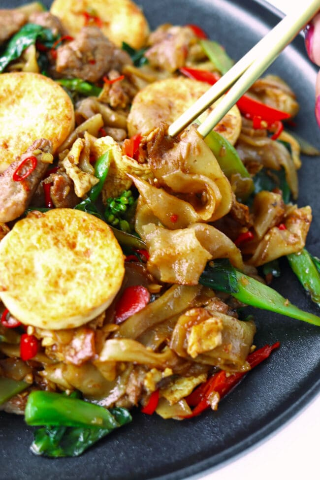 Chopsticks digging into plate with stir-fried rice noodles.