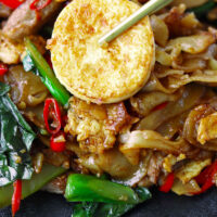 """Chopsticks holding up an egg tofu piece in a plate of noodles. Text overlay """"Pad See Ew"""", """"Thai Wok Fried Rice Noodles"""", and """"thatspicychick.com""""."""