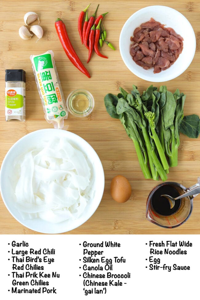 Labeled fresh and pantry ingredients for Pad See Eww on a wooden board.