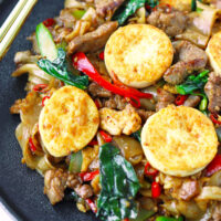 """Front view of plate with stir-fried noodles dish. Text overlay """"Pad See Ew"""", """"Thai Rice Noodles Stir-fry"""", and """"thatspicychick.com""""."""