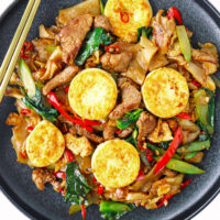 """Plate with stir-fried rice noodles dish. Text overlay """"Pad See Ew"""", """"With Pork & Pan-Fried Egg Tofu"""", and """"thatspicychick.com""""."""