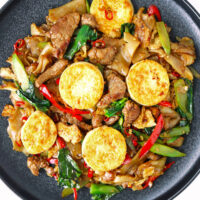 """Black plate with stir-fried rice noodles. Text overlay """"Pad See Ew"""", """"Thai Rice Noodles Stir-fry"""", and """"thatspicychick.com""""."""