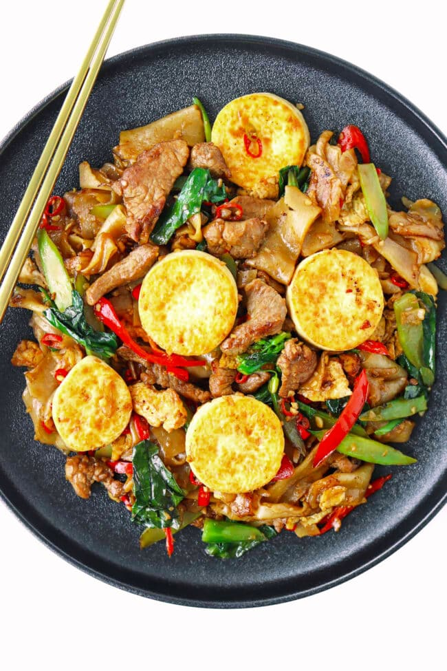 Plate with Pad See Ew with pork and crispy egg tofu. Chopsticks on side of plate.