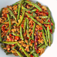 """Close-up top view of beans and pork stir-fry in a bowl. Text overlay """"Sichuan Dry Fried Green Beans & Pork"""" and """"thatspicychick.com""""."""