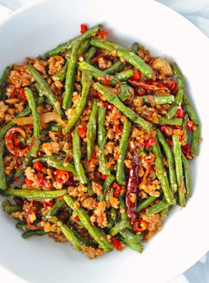 Close-up top view of green beans and ground pork stir-fry in a serving bowl.