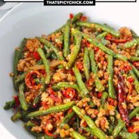 """Front view of bowl with beans and pork stir-fry. Text overlay """"Sichuan Dry Fried Green Beans with Pork"""" and """"thatspicychick.com""""."""