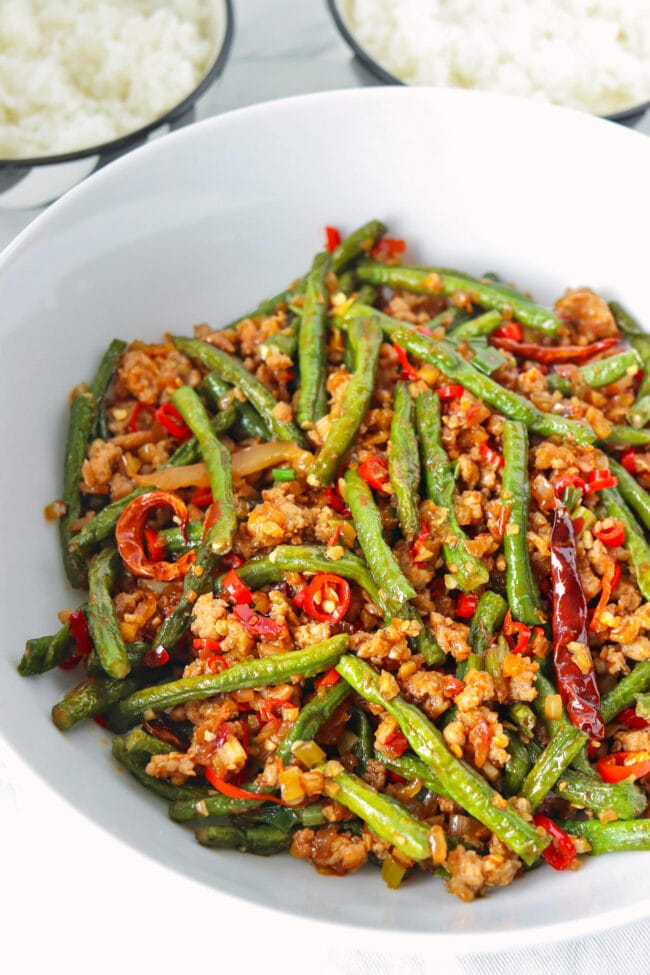 Close-up front view of green beans and ground pork stir-fry in a serving bowl.