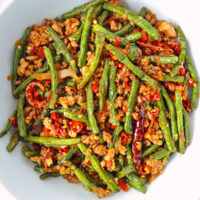"""Top view of beans and pork stir-fry in a bowl. Text overlay """"Sichuan Dry Fried Green Beans with Pork"""" and """"thatspicychick.com""""."""