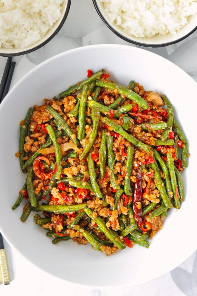 Top view of green beans and pork stir-fry in a serving bowl and two rice bowls.
