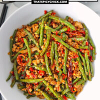 """Beans and pork stir-fry in a bowl, and two bowls of rice. Text overlay """"Sichuan Dry Fried Green Beans with Pork"""" and """"thatspicychick.com""""."""