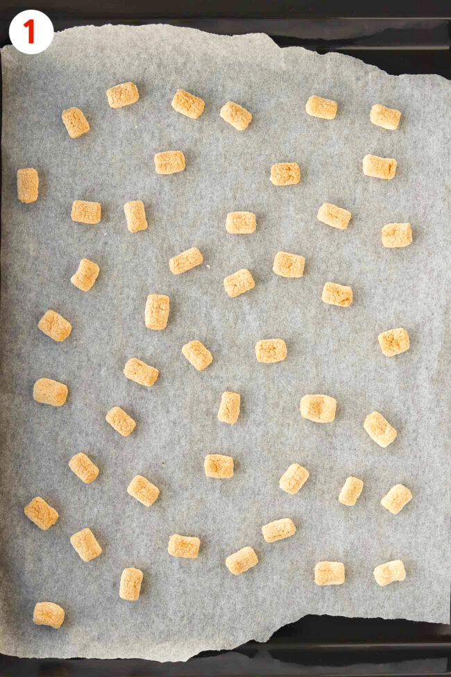 Toasted mini marshmallows on a parchment paper lined baking tray.