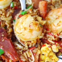 """Closeup of fried rice with shrimp on a spoon in a plate. Text overlay """"XO Sauce Fried Rice with Char Siu Pork & Shrimp"""" and """"thatspicychick.com""""."""
