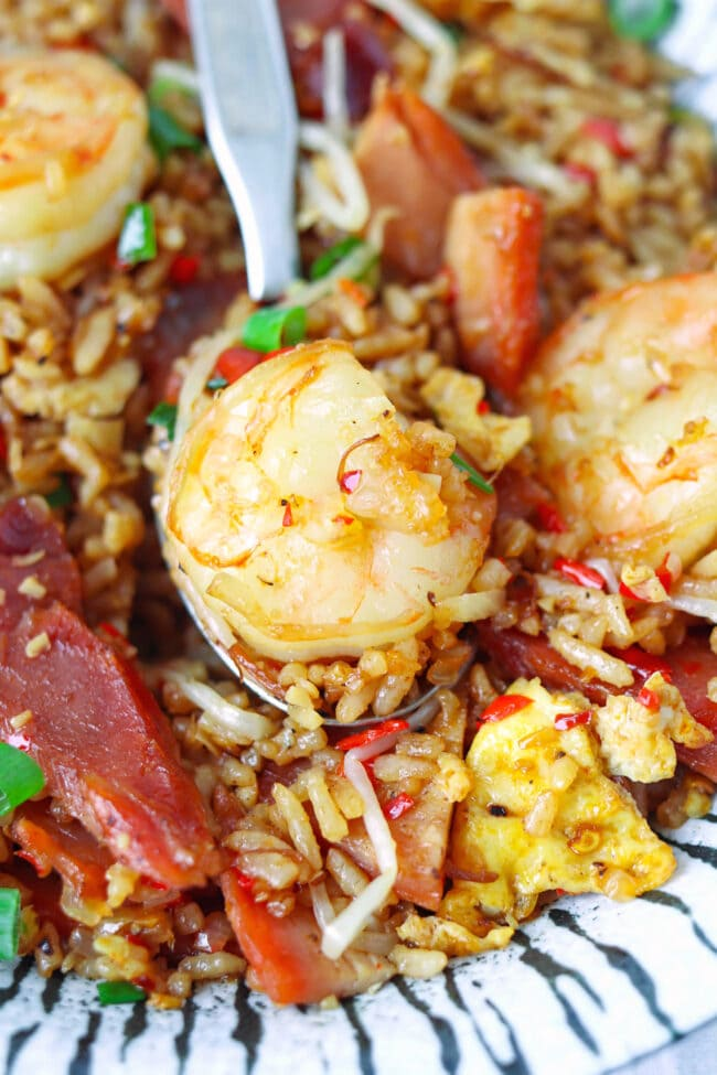 Close-up of fried rice with shrimp on a spoon in a plate.