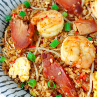 """Front view of fried rice on a plate. Text overlay """"XO Sauce Fried Rice with Chinese BBQ Pork & Shrimp"""" and """"thatspicychick.com""""."""