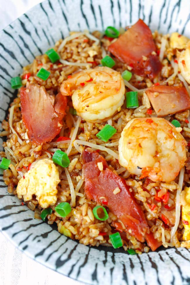 Close-up front view of fried rice with char siu pork and shrimp in a plate.