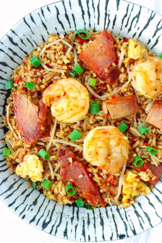 Close-up top view of fried rice with char siu pork and shrimp in a plate.