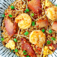 """Close-up top view of plate with fried rice. Text overlay """"XO Sauce Fried Rice with Chinese BBQ Pork & Shrimp"""" and """"thatspicychick.com""""."""