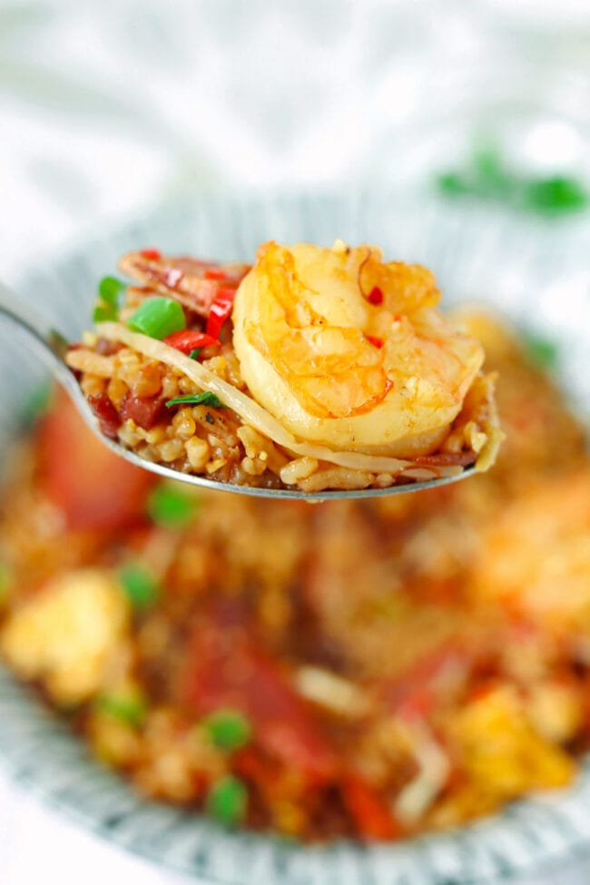 Spoon holding up a bite of fried rice with a jumbo shrimp.