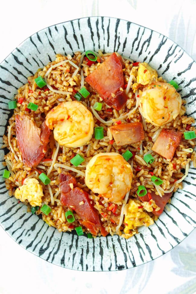 Top view of fried rice with char siu pork and shrimp on a plate.