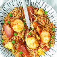 """Plate with fried rice and a spoon. Text overlay """"XO Sauce Fried Rice with Char Siu Pork & Shrimp"""" and """"thatspicychick.com""""."""