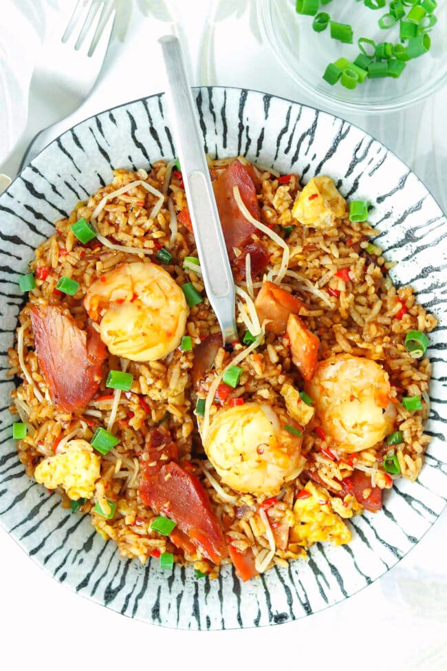 Top view of fried rice on a plate with a spoon, shrimp, and char siu pork.
