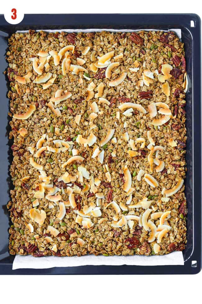 Baked apple pie granola on a parchment paper lined baking tray.