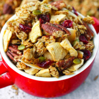"""Granola clusters in a red soup bowl. Text overlay """"Crunchy Apple Pie Granola"""", """"thatspicychick.com"""", and """"Healthy   Gluten-free   Vegan""""."""