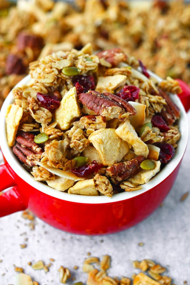 Close-up front view of apple pie granola in a bowl on a tray with granola.