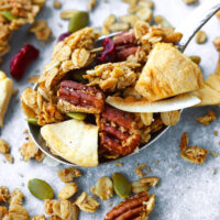 """Granola on a spoon and scattered on tray. Text overlay """"Crunchy Apple Pie Granola"""", """"thatspicychick.com"""", and """"Healthy   Gluten-free   Vegan""""."""
