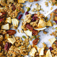 """Top view of granola on a spoon on a tray with granola scattered around. Text overlay """"Apple Pie Granola"""", """"Healthy   Vegan   Gluten-free"""", and """"thatspicychick.com""""."""