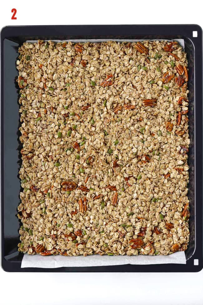 Unbaked granola mixture on a parchment paper lined baking tray.