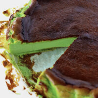 """Slice of cake cut out to show inside. Text overlay """"Basque Burnt Cheesecake"""", """"Pandan Flavored"""", and """"thatspicychick.com""""."""