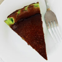 """Cake slice on plate with a fork. Text overlay """"Basque Burnt Cheesecake"""", """"Pandan Edition"""", and """"thatspicychick.com""""."""