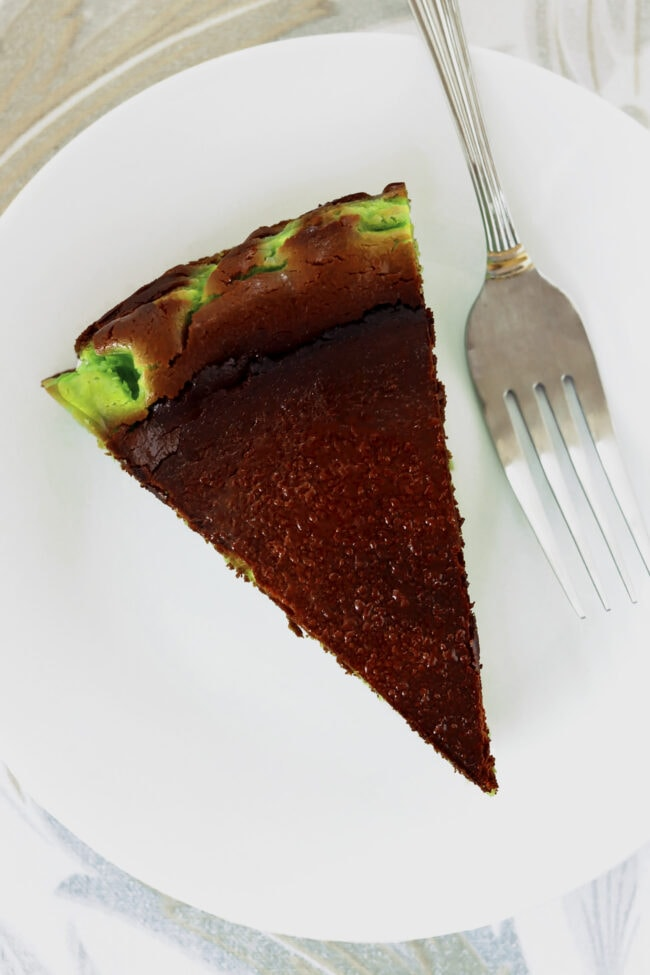 Top view of pandan burnt cheesecake slice and a fork on a plate.