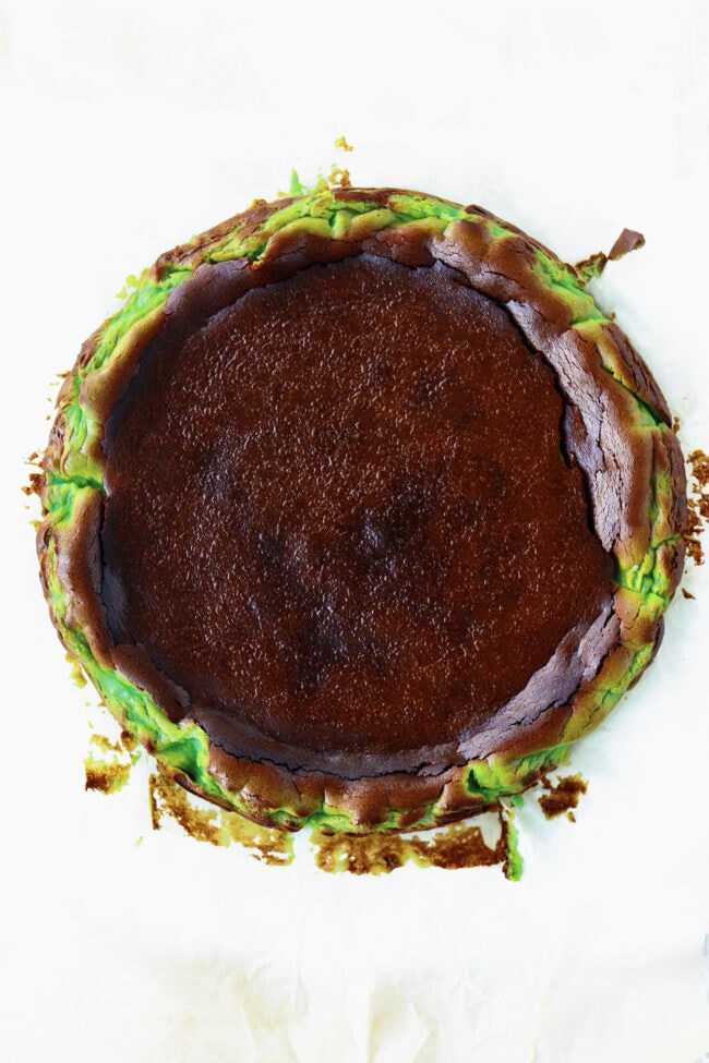 Top view of whole pandan burnt cheesecake on a sheet of parchment paper.