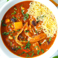 """Close-up top view of soup in bowl. Text overlay """"Spicy Chicken Enchilada Soup"""" and """"thatspicychick.com""""."""