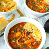 """Front view of two bowls with soup. Text overlay """"Spicy Chicken Enchilada Soup"""" and """"thatspicychick.com""""."""