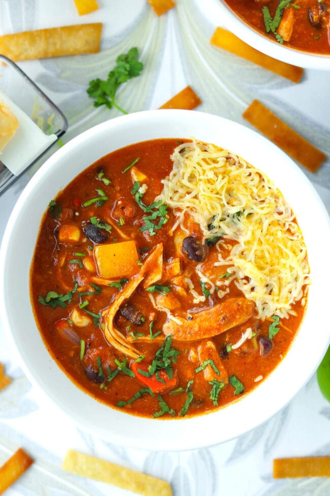 Bowls with soup garnished with cheese and cilantro. Tortilla strips scattered around bowls.