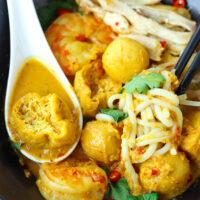 """Close-up of spoon with tofu puff and broth in a bowl of soup noodles. Text overlay """"Spicy Laksa"""", """"Coconut Curry Noodle Soup"""", and """"thatspicychick.com""""."""