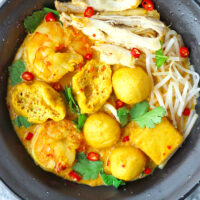 Closeup top view of spicy curry laksa in black bowl with garnishes.