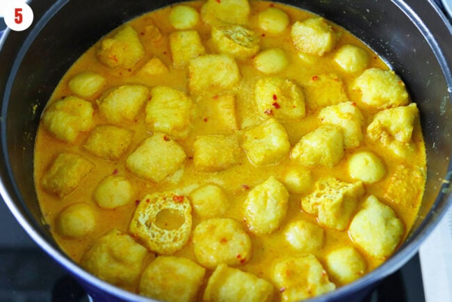 Laksa broth simmering in a Dutch oven with tofu puffs, fish balls, and fish tofu.