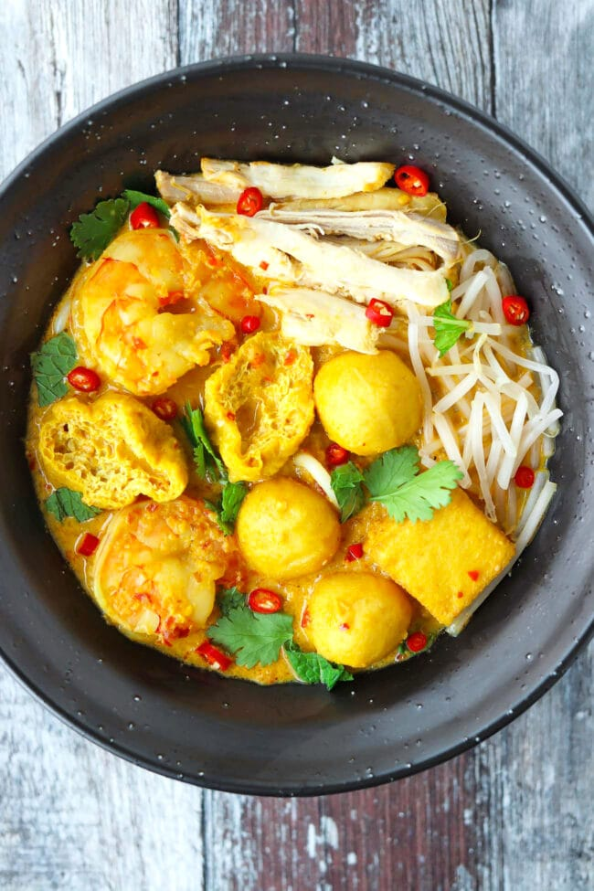 Top view of a fully garnished bowl of laksa.